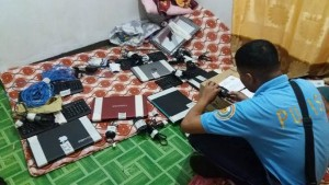 A policeman takes a photo of seized laptops and tablet computers in the house of a PO2 Joel Belleno in Zamboanga del Norte's Latipunan town in these police photos released to the media. (Ely Dumaboc)